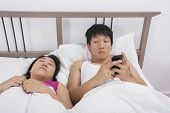 Man using cell phone while looking at woman sleeping in bed