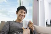 Portrait of mid adult man holding coffee cup in house
