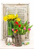 Spring Flowers And Colored Easter Eggs. Tulips And Narcissus