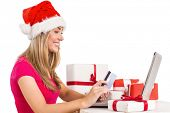 Festive blonde shopping online with laptop on white background