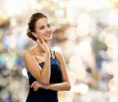 people, holidays and glamour concept - smiling woman in evening dress over black background over lights background