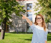 education, school and imaginary screen concept - cute little girl in eyeglasses pointing in the air