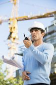 Male architect holding blueprints while using walkie-talkie at construction site