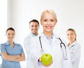 healthcare and medicine concept - smiling female doctor with stethoscope and green apple