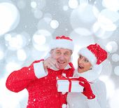 Festive mature couple holding gift against white glowing dots on grey