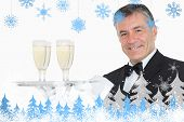 Waiter holding tray with glasses full of champagne against snowflakes and fir trees