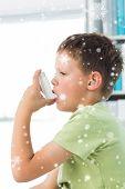Boy using asthma inhaler in hospital against snow falling