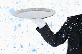 Hand with white gloves holding a silver tray against snow falling