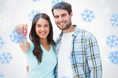 Happy young couple showing new house key against snowflakes