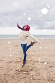 Woman in stylish warm clothing jumping at beach against snow falling