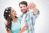 Happy young couple showing new house key against snow falling