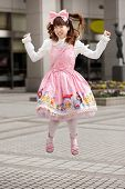 stock photo of lolita  - Happy japanese sweet lolita cosplay jumping on a Tokyo sidewalk - JPG