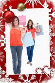 Smiling teenagers holding purchase bags in the air against christmas themed page