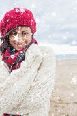 Cute smiling woman in stylish warm clothing on the beach against snow falling