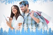 Attractive young couple with shopping bags and tablet pc against frost and fir trees