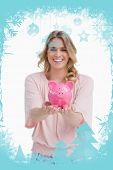A smiling woman is holding a piggy bank in the palms of her hands against christmas frame