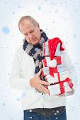 Mature man in winter clothes holding gifts against snow falling