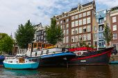 picture of houseboats  - City view of Amsterdam canals and typical houses houseboat and boats Holland Netherlands - JPG
