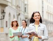 tourism, travel, leisure and holidays and friendship concept - smiling teenage girls with city guide