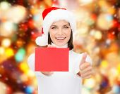 christmas, holdays, people, advertisement and sale concept - happy woman in santa helper hat with blank red card showing thumbs up gesture over lights background