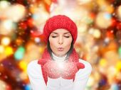 happiness, winter holidays, christmas and people concept - smiling young woman in red hat, scarf and mittens over lights background