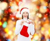 christmas, winter, happiness, holidays and people concept - smiling woman in santa helper hat with small gift box and stocking over red lights background