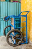 picture of tricycle  - Vietnamese delivery tricycle at old apartment in Saigon - JPG