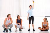 Group Of Diverse People Looking Woman Lifting Kettlebell In Gym