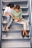Two Women Sitting Staircase Using Digital Tablet