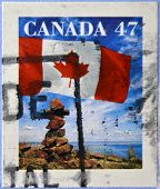 CANADA - CIRCA 2000: A stamp printed in Canada shows the flag fluttering over an inukshuk circa 2000