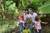 Group of happy people, farmer and customer family, in banana plantation
