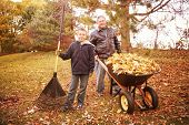 Father and son raking leaves