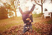 Boy throwing autumn leaves