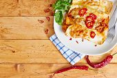stock photo of enchiladas  - Enchiladas with cream and red peppers on wooden table - JPG