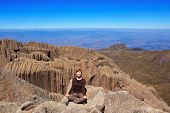 Young Smiling Woman Sitting On Edge Of The Mountain Yoga Pose