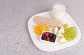 Slices of fruits with crispbreads and glass of milk on plate on table close up