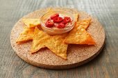 Tasty nachos and bowl with sauce on board, on wooden background