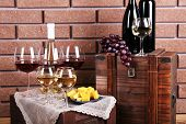 Bottles and glasses of wine, cheese and ripe grapes on table on brick wall background