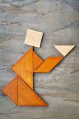 abstract picture of a figure offering a cup of tea or soup built  from seven tangram wooden pieces a