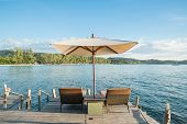 Two Chairs Beach And Umbrella On Wooden Desk Against Blue Sky.summer Travel In Phuket ,thailand.