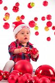 Little boy playing with christmas baubles.