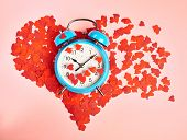 Alarm clock over the heart shape