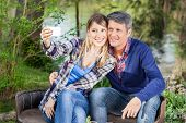 Happy couple taking selfportrait through smartphone while sitting on chairs at campsite