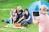 Grandmother photographing family through digital tablet at campsite