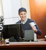 Happy male worker holding tickets at box office counter