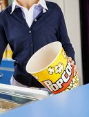 Midsection of female worker holding empty popcorn bucket at cinema concession stand