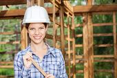 Portrait of happy female construction worker holding measuring tape at site