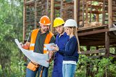 stock photo of blueprints  - Male and female architects using digital tablet while reviewing blueprint at construction site - JPG