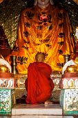 YANGON, MYANMAR - JANUARY 3, 2014: Buddhist monk praying in Shwedagon Paya pagoda. Yangon, Myanmar