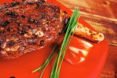 savory on red plate: grilled meat shoulder with tomato and chives on wooden table